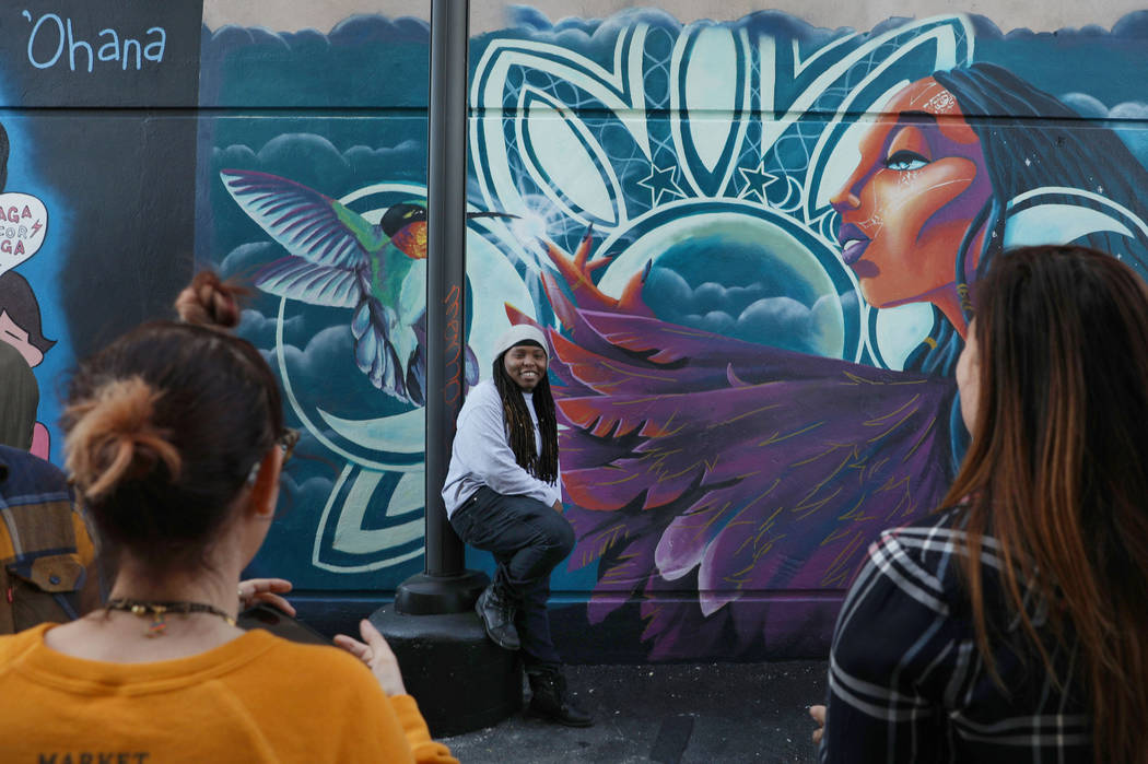 Local painter Sloane Siobhan is photographed in front of her mural during the grand opening of ...