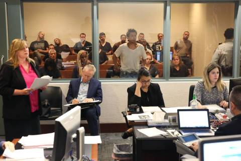 Defense attorney Leslie Park, left, addresses the court as her client, center, appears behind a ...
