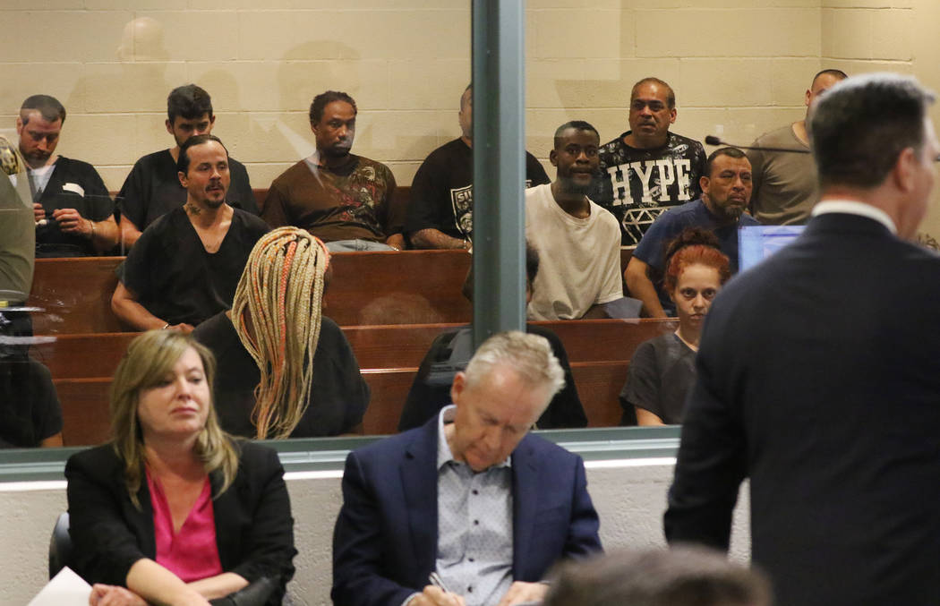 Suspects sit behind a partition glass during their initial appearance at the Regional Justice C ...