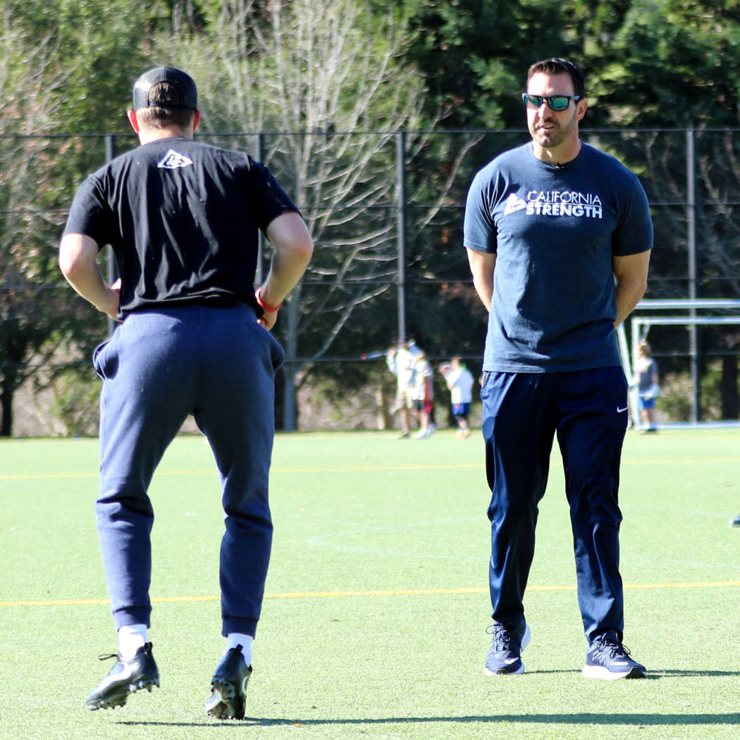 Strength and conditioning coach David Spitz, right, works with football players to prepare them ...