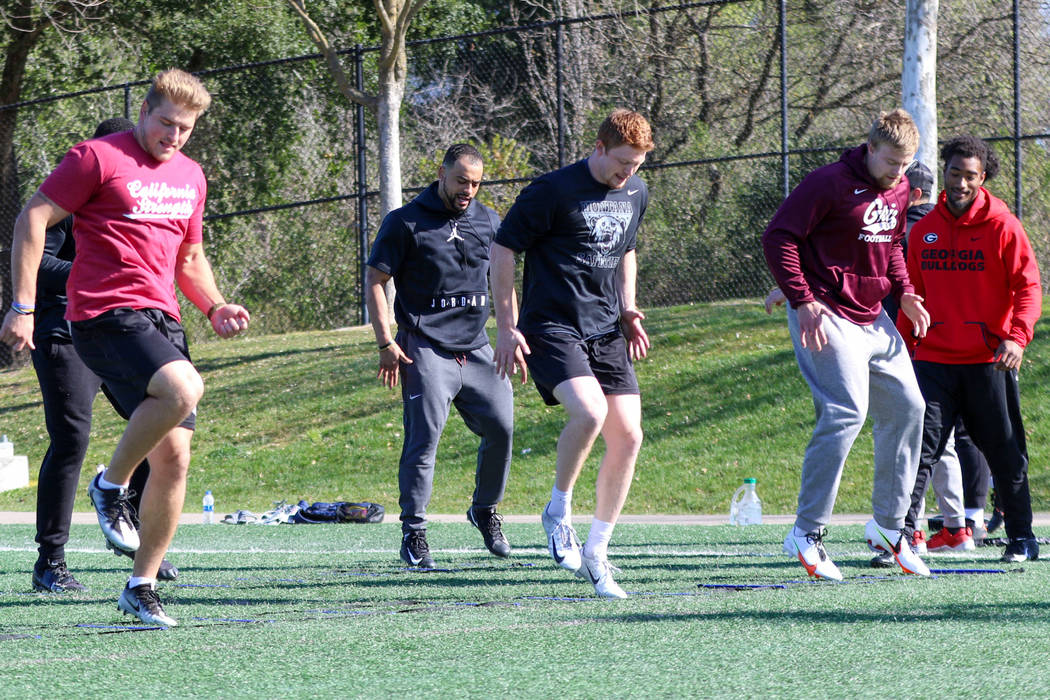 Football players Logan Wilson, from left, Cameron Scarlett, Josh Sandry and Dante Olson run thr ...