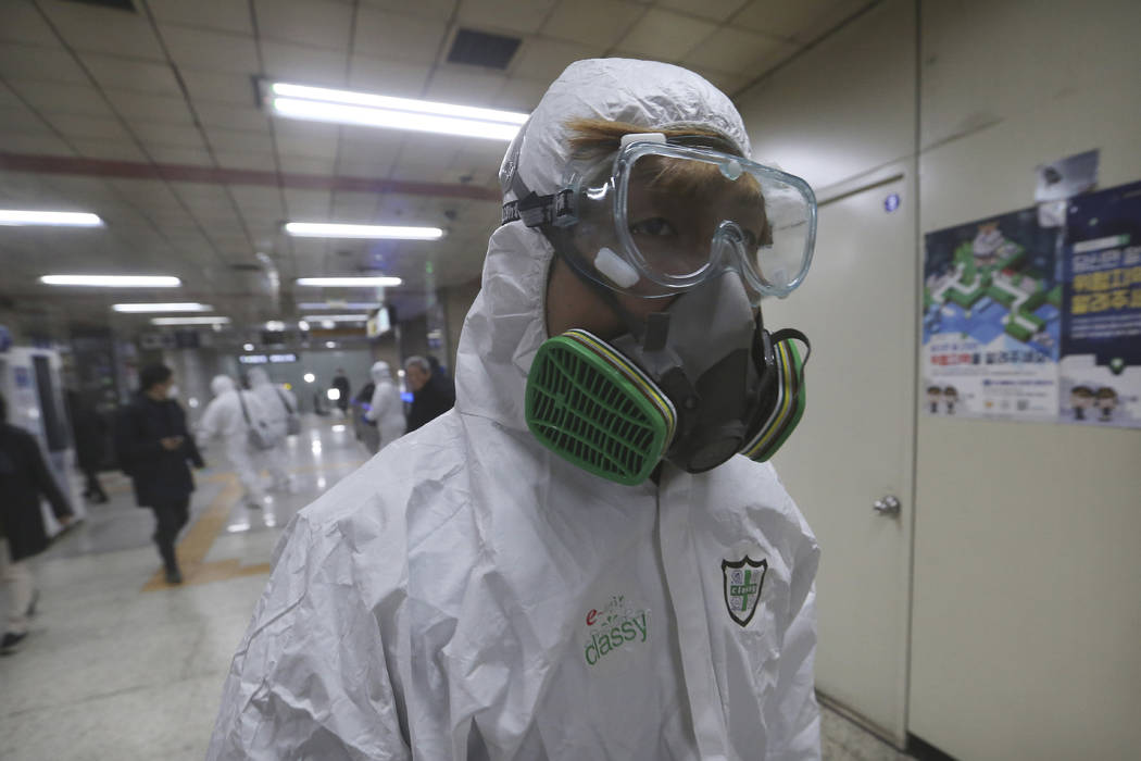 A workers wearing protective gears arrives to spray disinfectant as a precaution against the co ...