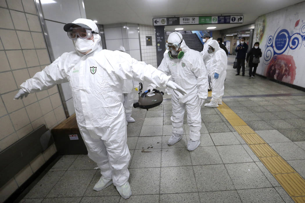 Workers wearing protective gears help clean each other's suits after disinfecting as a precauti ...