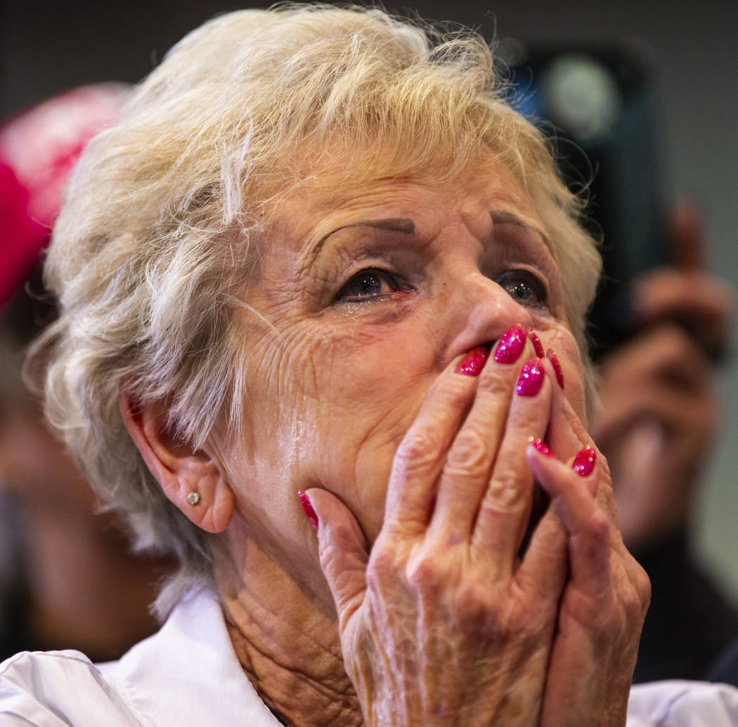 A supporter of President Donald Trump, not pictured, tears up while listening to him speak duri ...