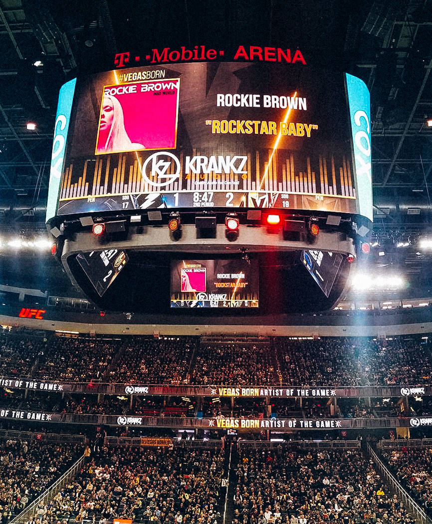 The T-Mobile Arena scoreboard is shown as Vegas Golden Knights music director Jake Wagner plays ...