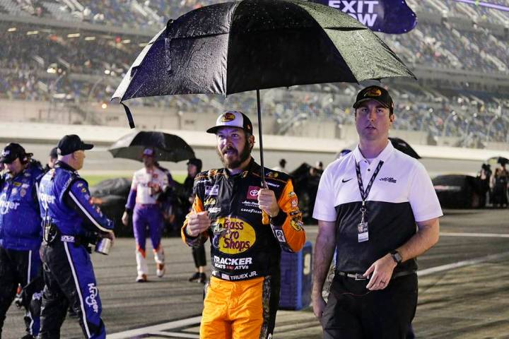 Martin Truex Jr.,center, walks with a crew member down pit road as rain delays the start of the ...