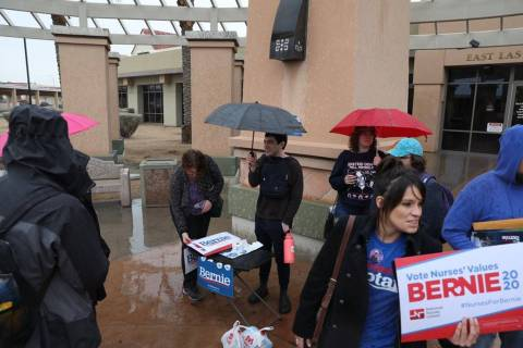 People gather in the rain at the East Las Vegas Community Center for the Nevada Democratic cauc ...
