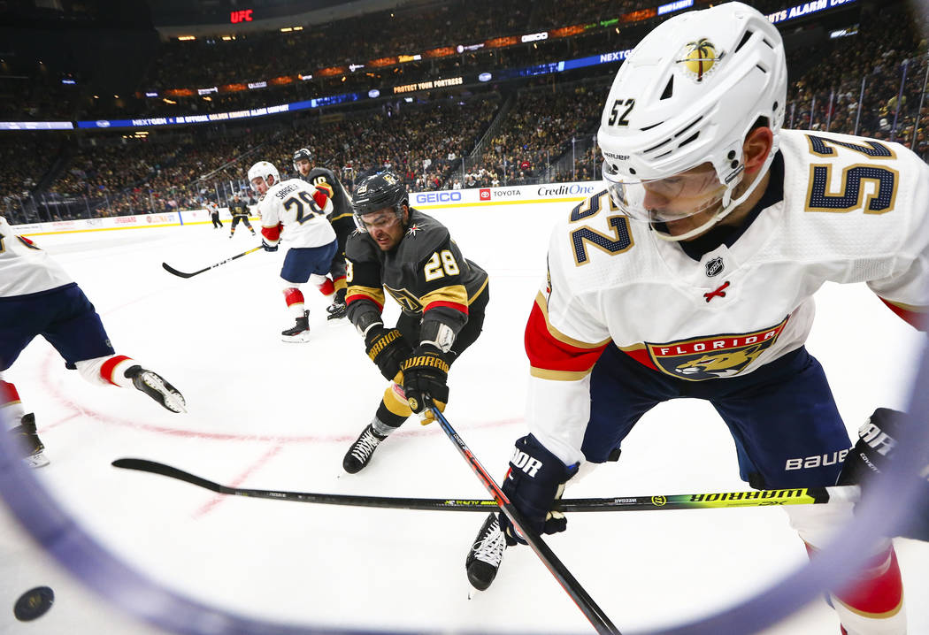 Golden Knights' William Carrier (28) and Florida Panthers' MacKenzie Weegar (52) battle for the ...