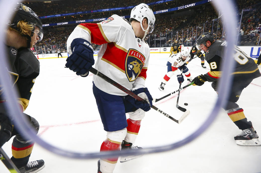 Golden Knights' Nate Schmidt (88) battles for the puck against Florida Panthers' Vincent Troche ...