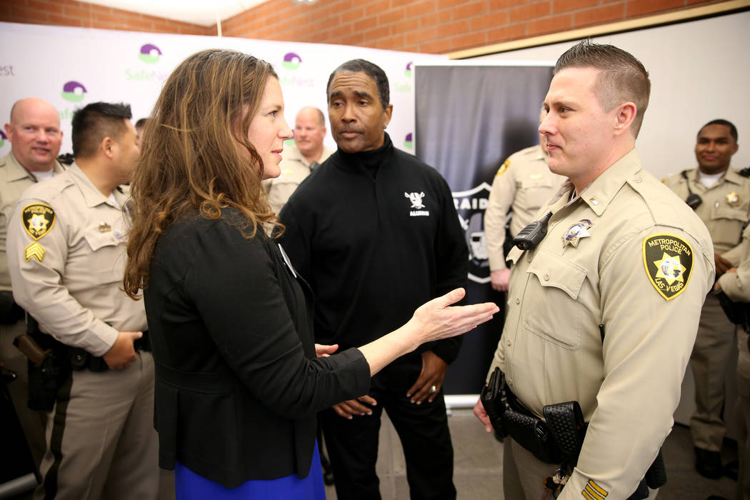 SafeNest CEO Liz Ortenburger visits with Las Vegas police Lt. Timothy Hatchett and Raiders alum ...