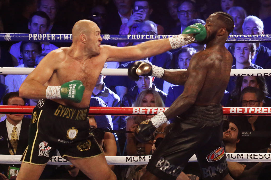 Tyson Fury, left, connects with a jab against Deontay Wilder in the first round during their WB ...