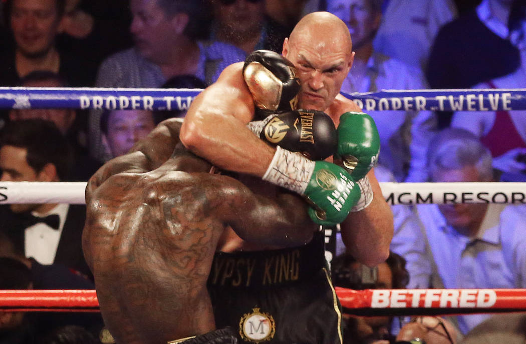 Tyson Fury, top/right, connects with a right hook against Deontay Wilder in the fourth round du ...