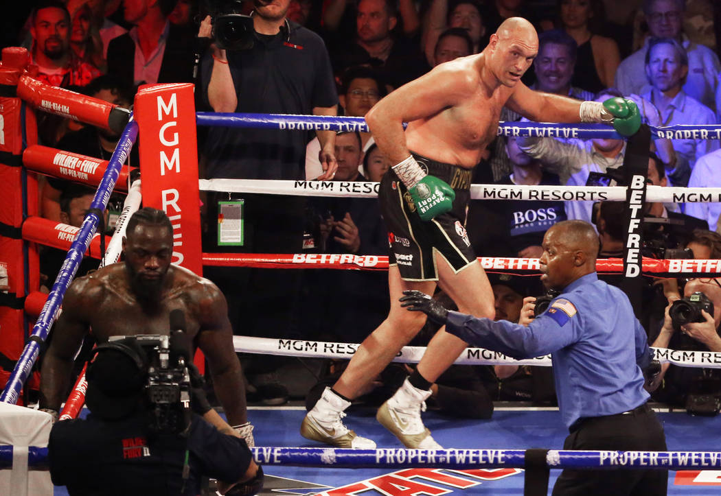 Tyson Fury, top/right, runs to his corner after knocking down Deontay Wilder in the fifth round ...