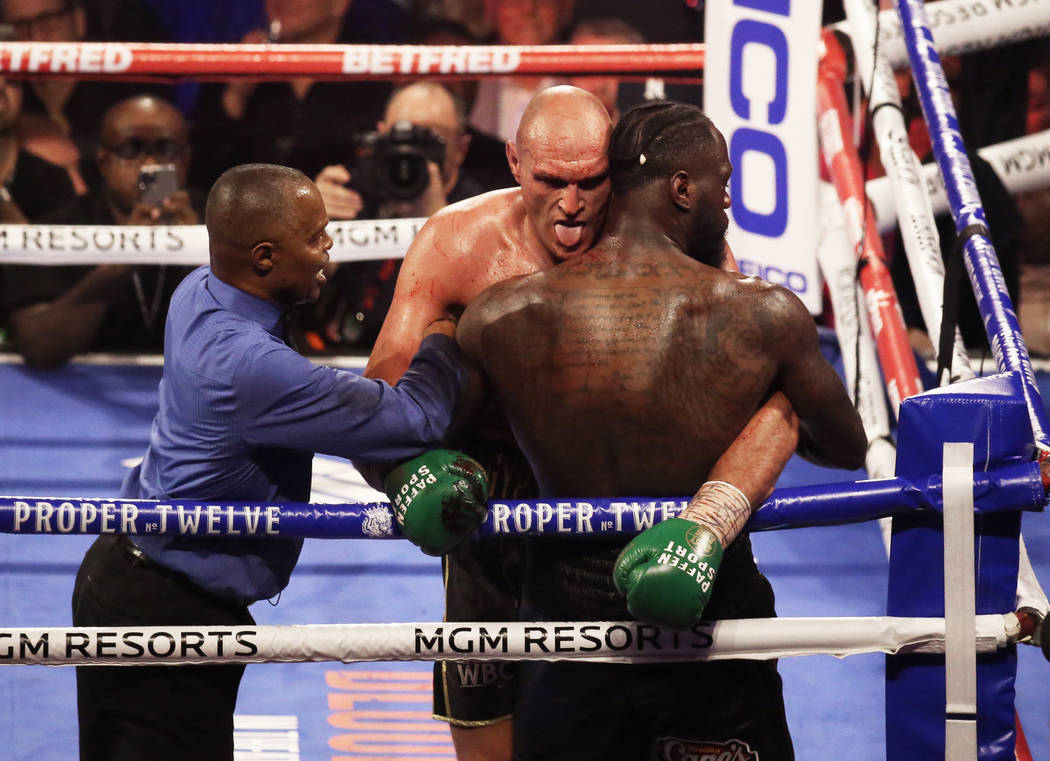Tyson Fury, left, sticks his tongue out while leaning on Deontay Wilder in the fifth round duri ...