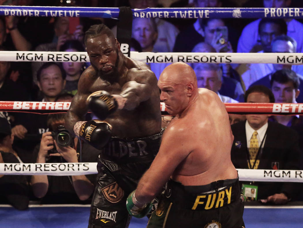 Deontay Wilder, left, connects with a left hook against Tyson Fury in the seventh round during ...