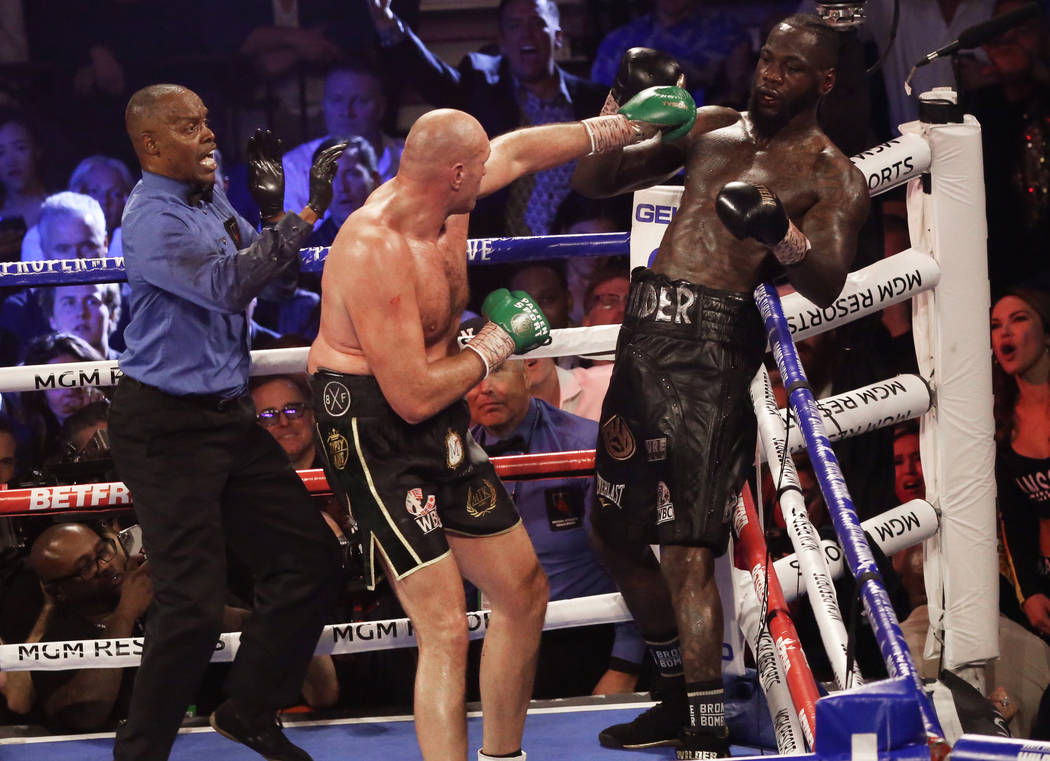 Tyson Fury lands a left hook against Deontay Wilder seconds before the fight was called in the ...