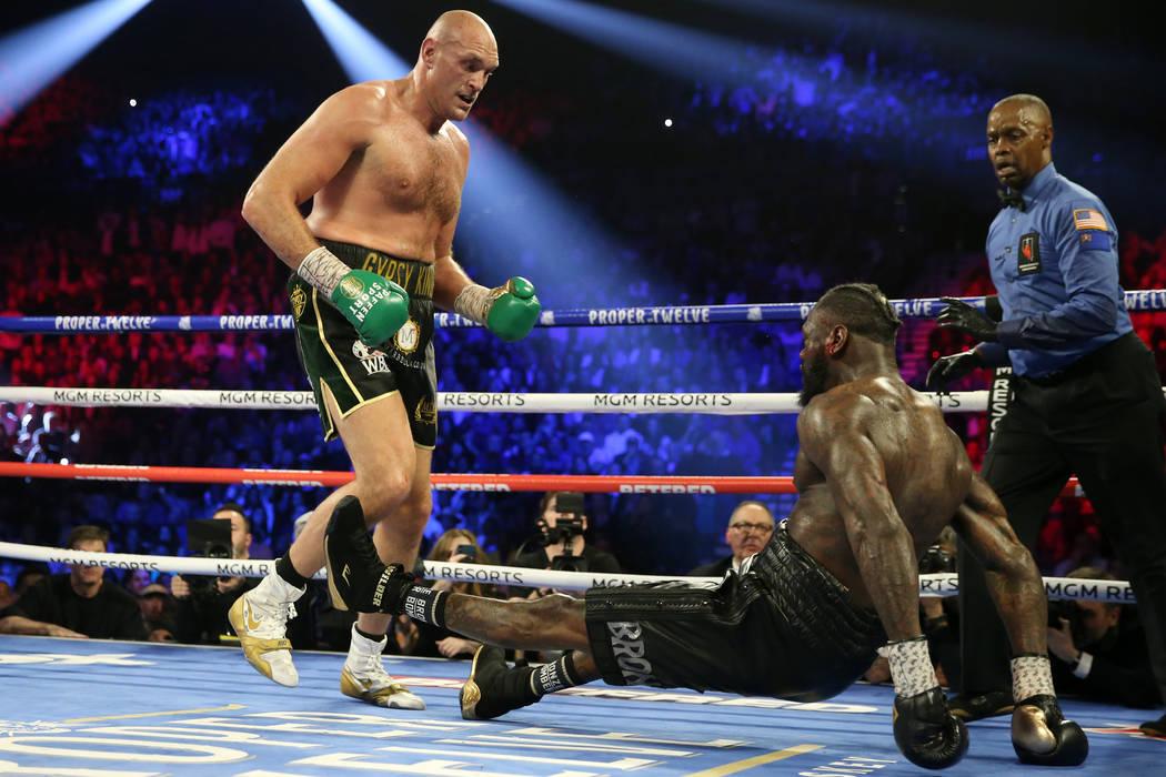 Tyson Fury, left, knocks down Deontay Wilder in round 5 of the WBC world heavyweight championsh ...