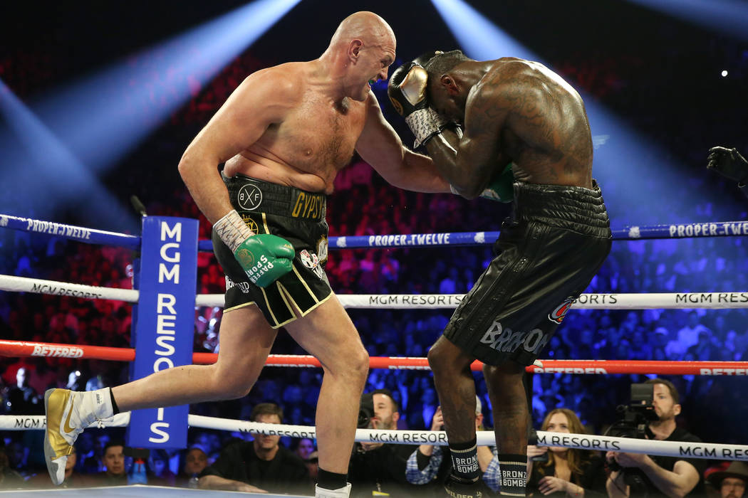 Tyson Fury, left, connects a punch to knock down Deontay Wilder in round 5 of the WBC world hea ...