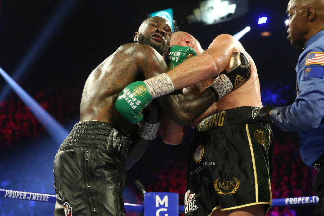 Tyson Fury, right, connects a punch against Deontay Wilder in round 5 of the WBC world heavywei ...