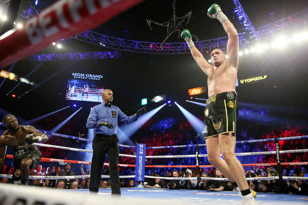 Tyson Fury, right, raises his hands after knocking down Deontay Wilder in round 3 of the WBC wo ...