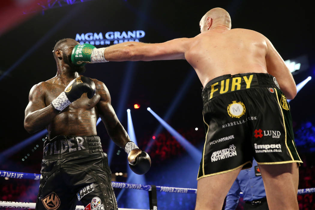 Tyson Fury, right, connects a punch against Deontay Wilder in round 2 of the WBC world heavywei ...