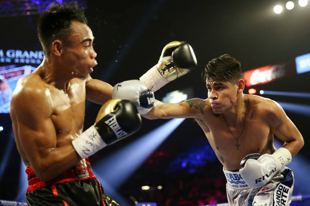 Emanuel Navarrete, right, connects a punch against Jeo Santisima in round 3 of the super bantam ...