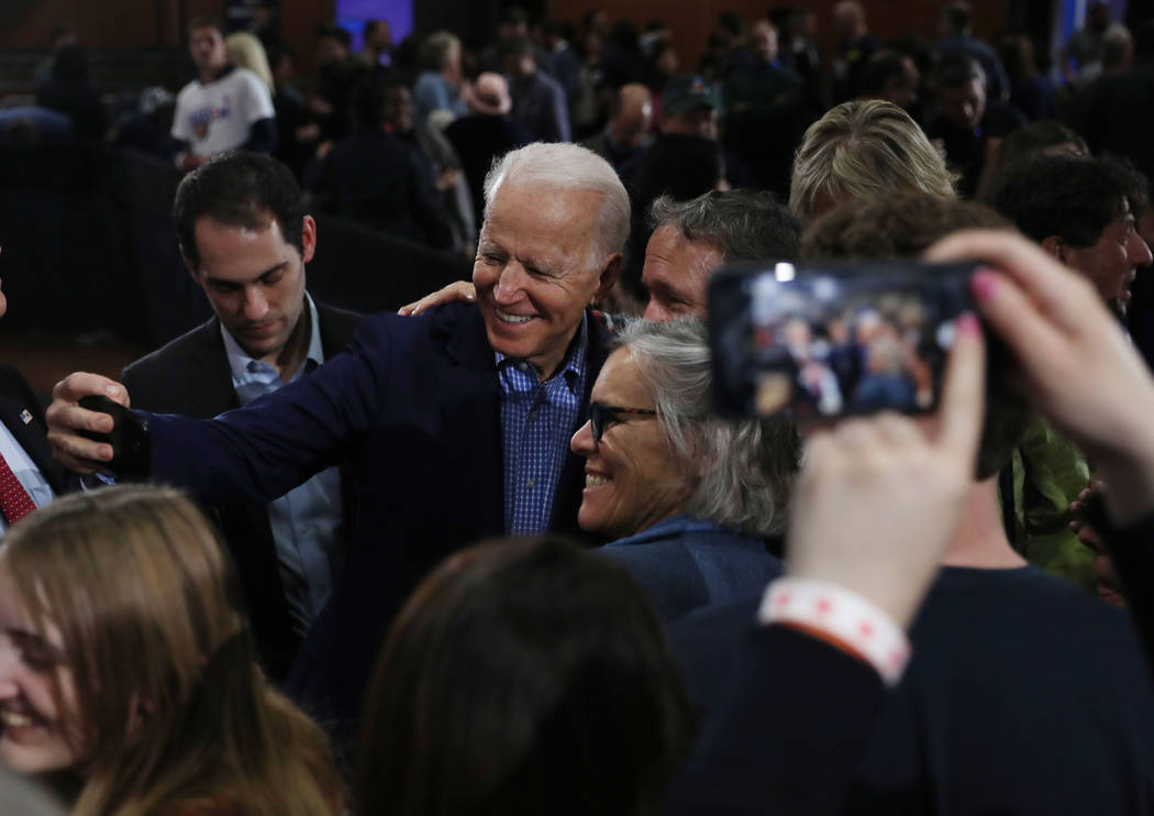 Joe Biden takes photographs with supporters during a caucus night event at IBEW local 357 in La ...
