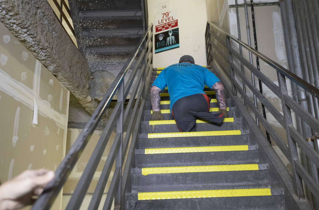 Travis Strong, a double amputee, climbs all of the stairs at the Strat with his arms on Sunday, ...