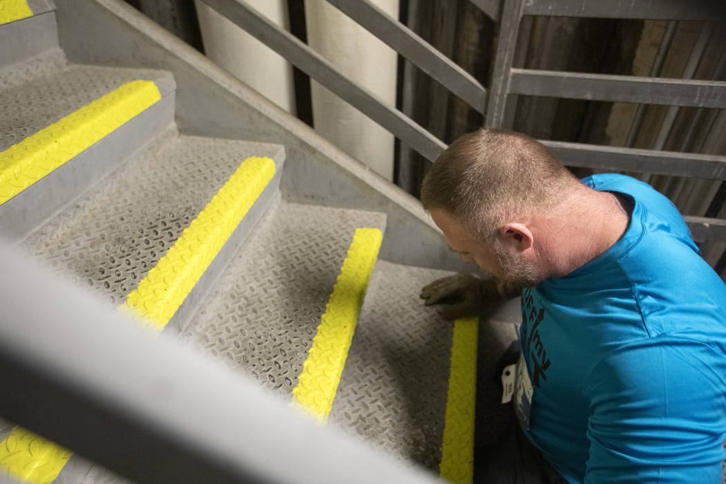 Travis Strong pauses to rest while climbing the 1,455 stairs at the Strat with his arms on Sund ...