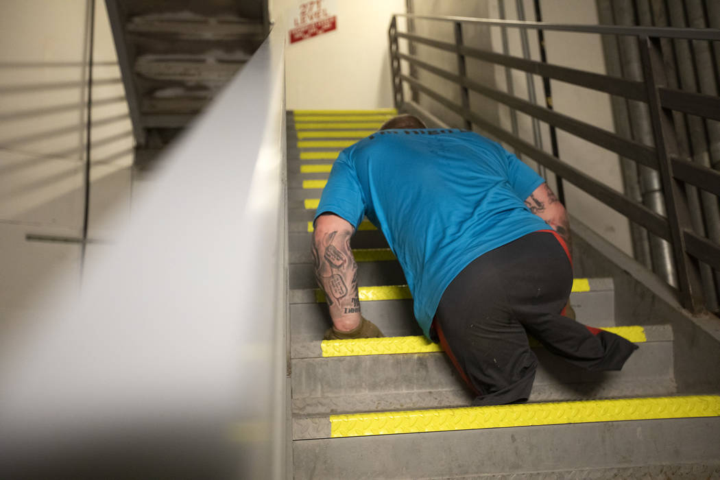 Travis Strong, a double amputee, makes way up the stairs at the Strat with his arms on Sunday, ...