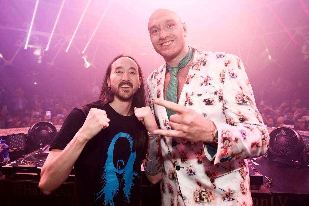 Tyson Fury, right, and DJ superstar Steve Aoki are shown celebrating his seventh-round TKO vict ...