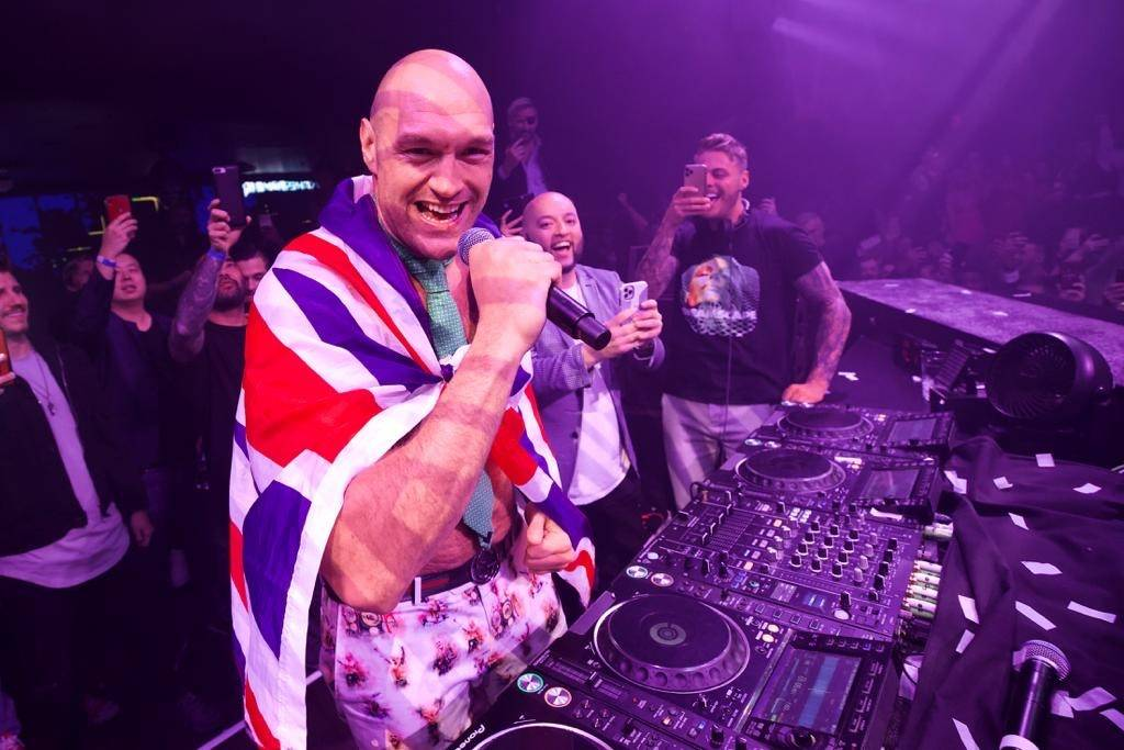 Tyson Fury (center, in Union Jack cape) is shown celebrating his seventh-round TKO victory over ...
