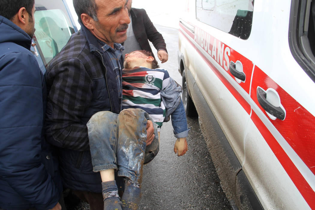 A man carries a wounded boy to an ambulance after an earthquake hit villages in Baskale town in ...
