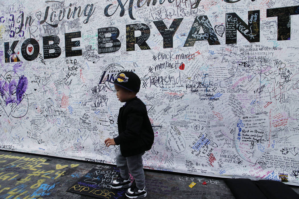 A boy walks by a standing board with messages for the late Kobe Bryant at a memorial for Bryant ...