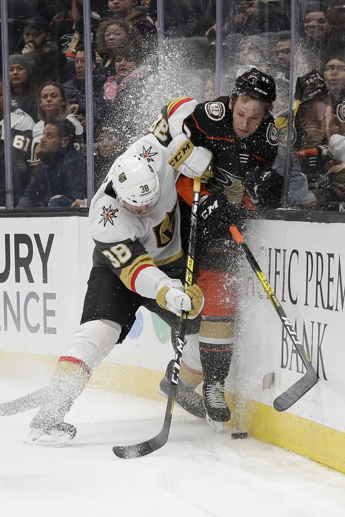 Vegas Golden Knights center Patrick Brown, left, checks Anaheim Ducks defenseman Jacob Larsson ...