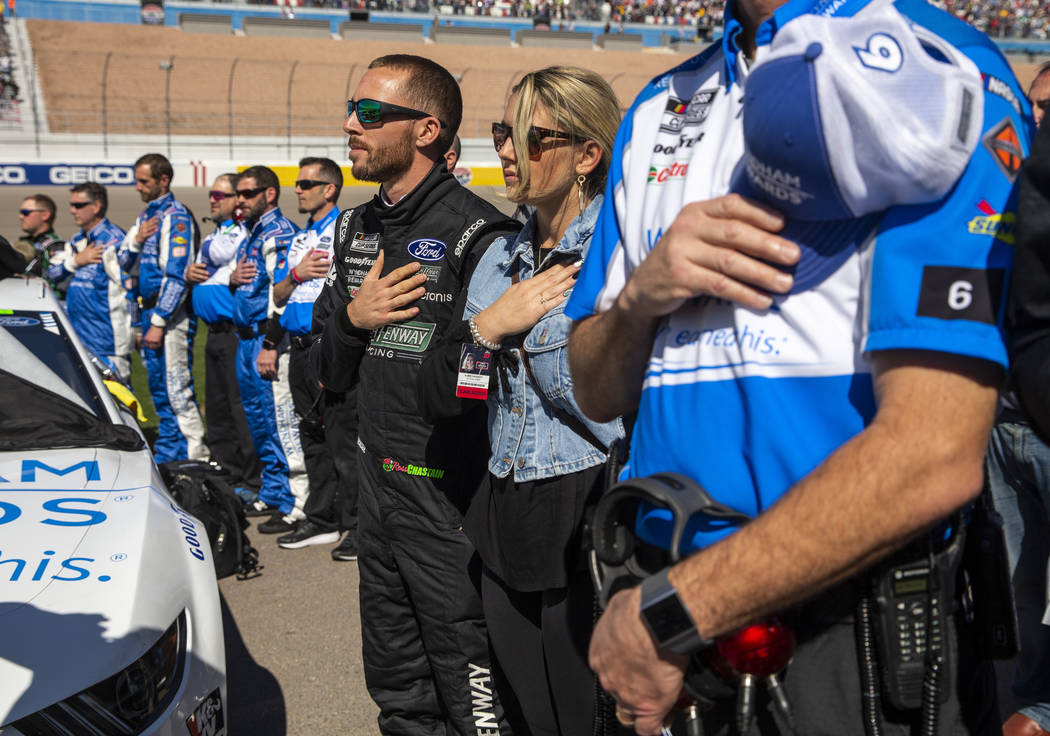 Ross Chastain (6, center) listens to the National Anthem with his crew before the start of the ...