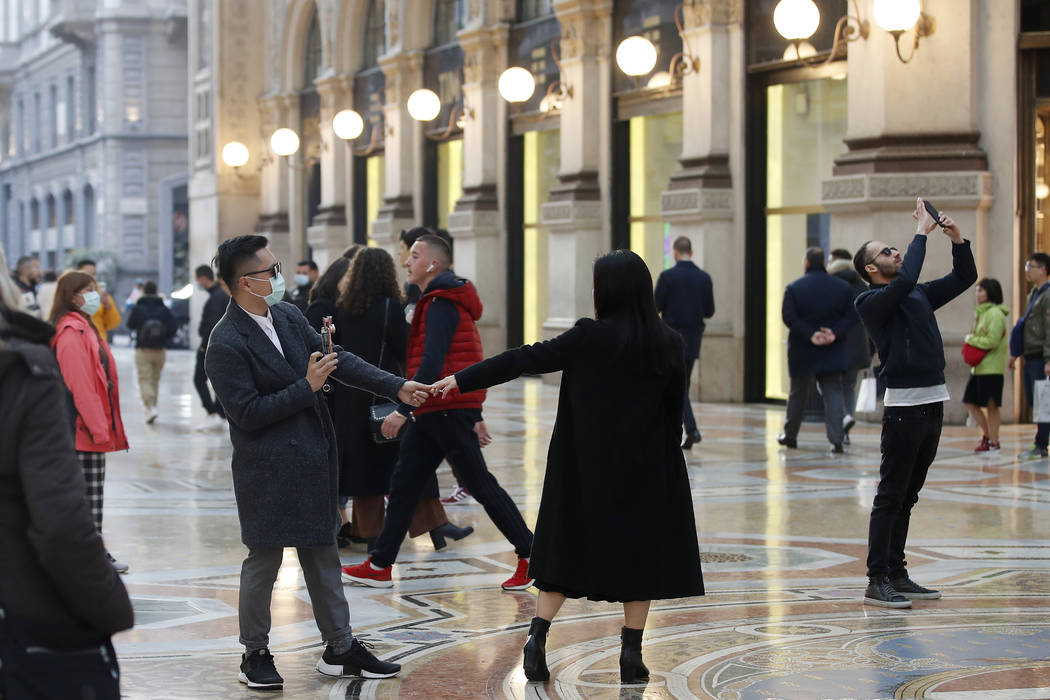Tourists wearing sanitary masks move a few steps of dance, in downtown Milan, Italy, Sunday, Fe ...
