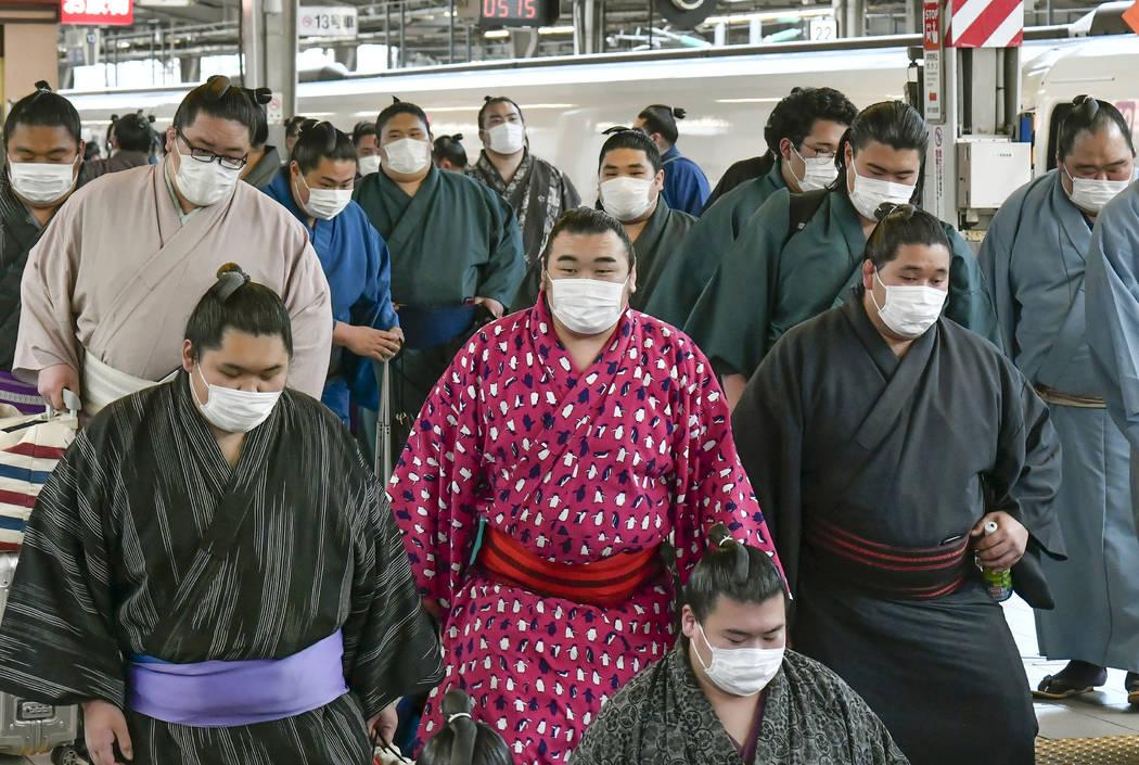In this Sunday, Feb. 23, 2020, photo, sumo wrestlers wearing masks arrive at Shin Osaka railway ...