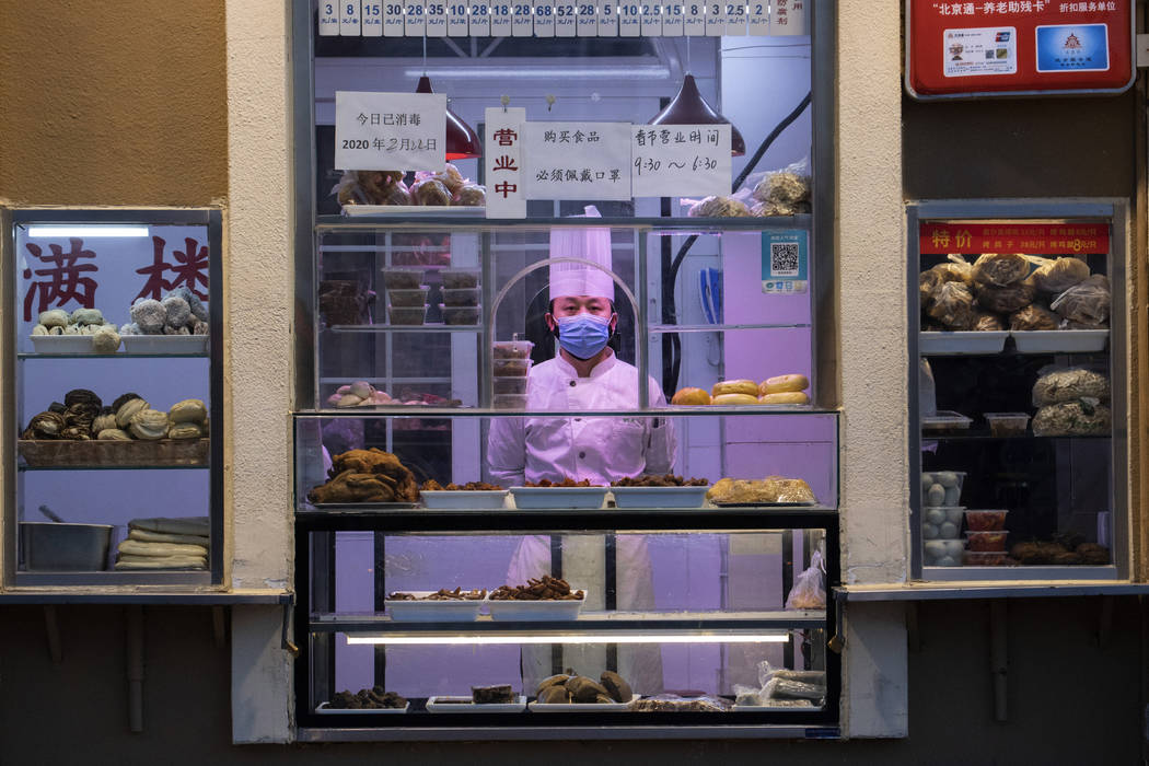 In this photo taken Saturday, Feb. 22, 2020, a chef looks out from behind a display of food pro ...