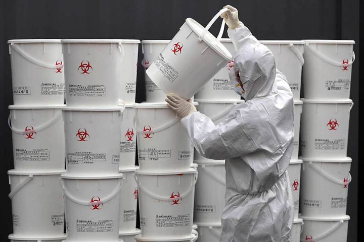 A worker in protective gear stacks plastic buckets containing medical waste from coronavirus pa ...