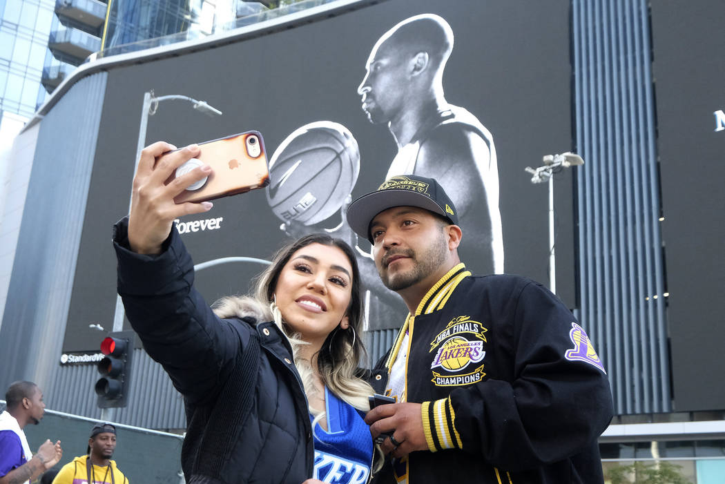 Alyssa Quevedo and her husband Emmanuel take a selfie in front of a mural of Kobe Bryant near t ...