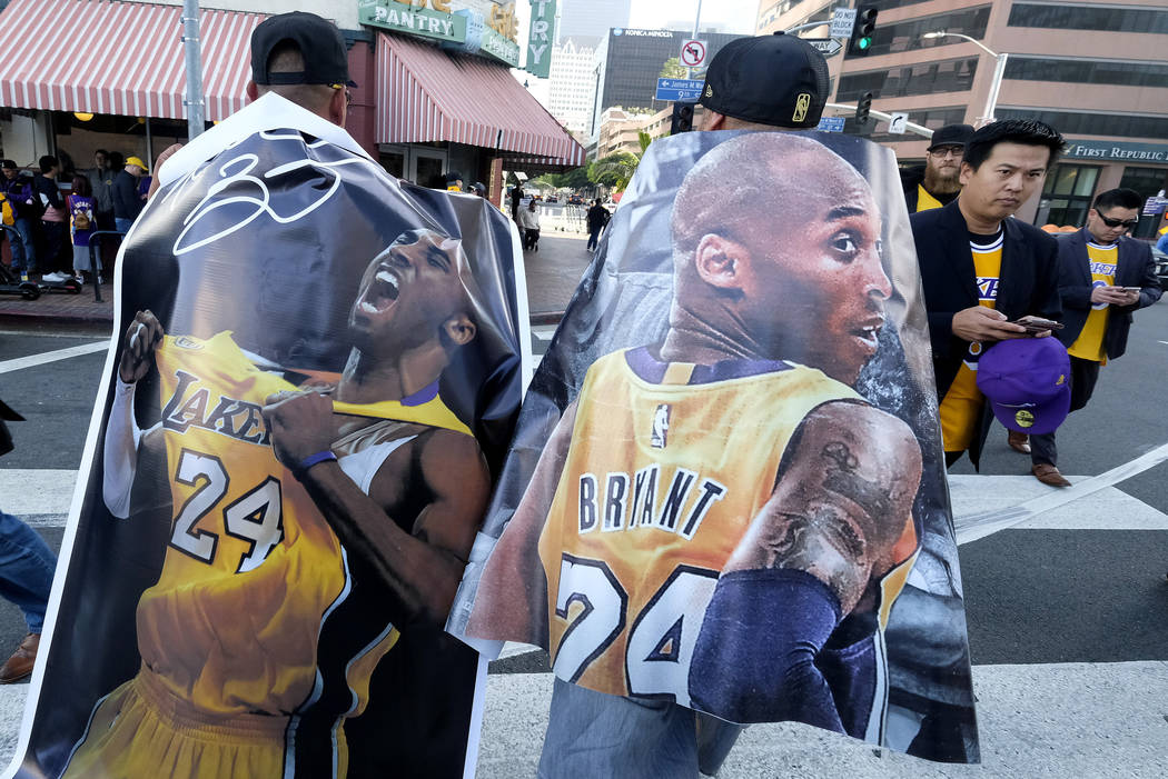 Fans carry posters of Kobe Bryant near the Staples Center before a public memorial for former L ...