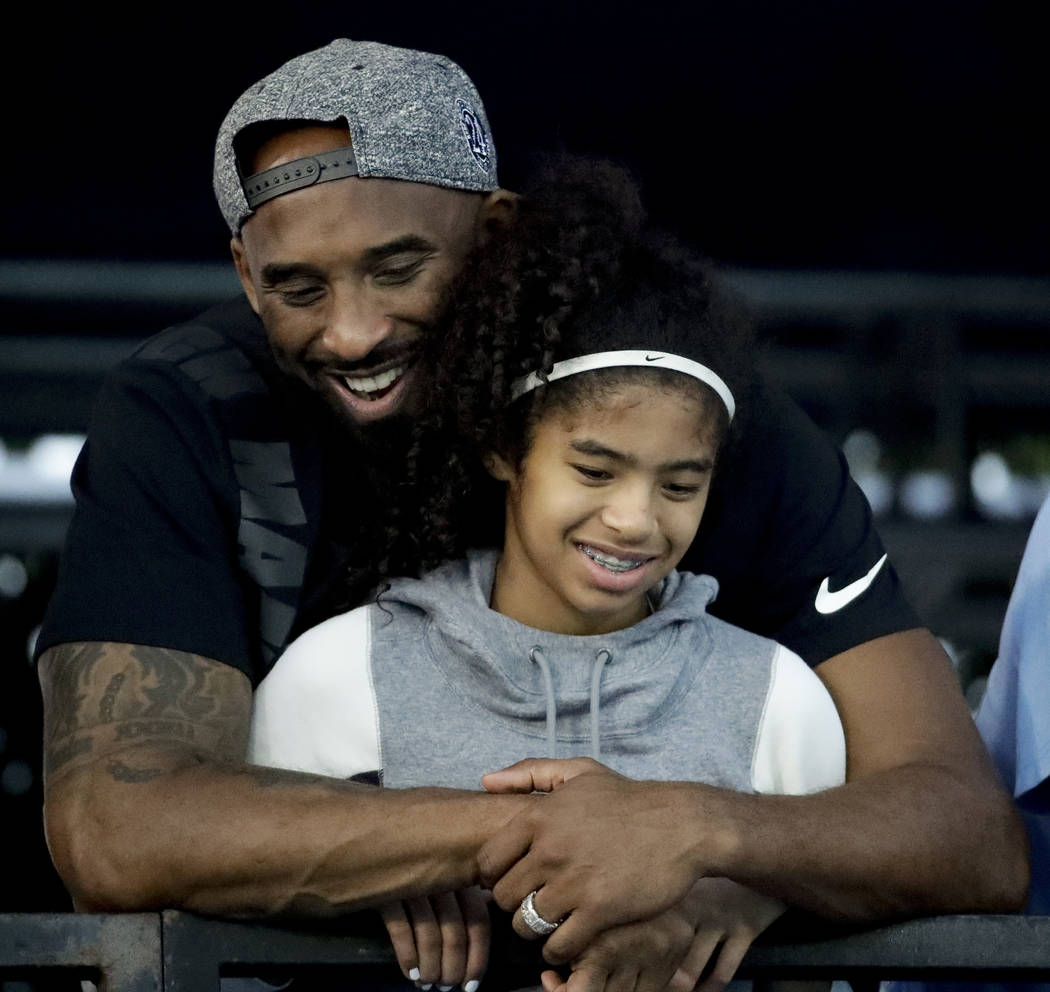 Former Los Angeles Laker Kobe Bryant and his daughter Gianna watch during the U.S. national cha ...
