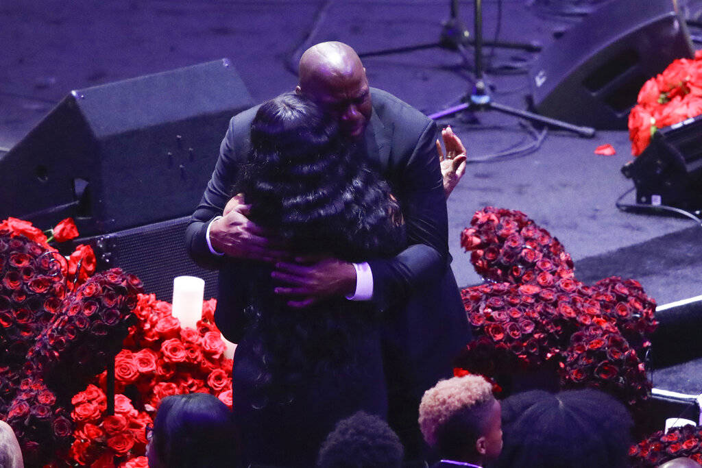 Former Los Angeles Lakers' Magic Johnson hugs Pam Bryant mother of Kobe Bryant during a celebra ...