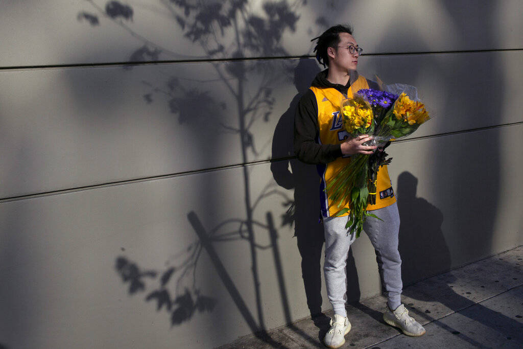 David Chen holds flowers bearing Lakers colors near the Staples Center before a public memorial ...