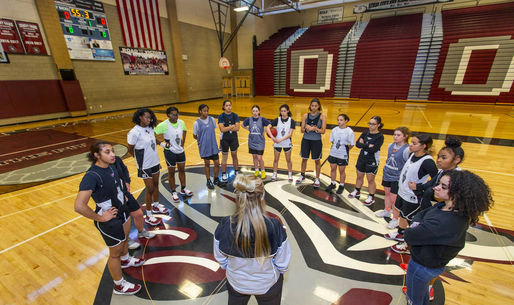 Head coach Laurie Evans, center, talks to her players during a Desert Oasis girl's basketball t ...