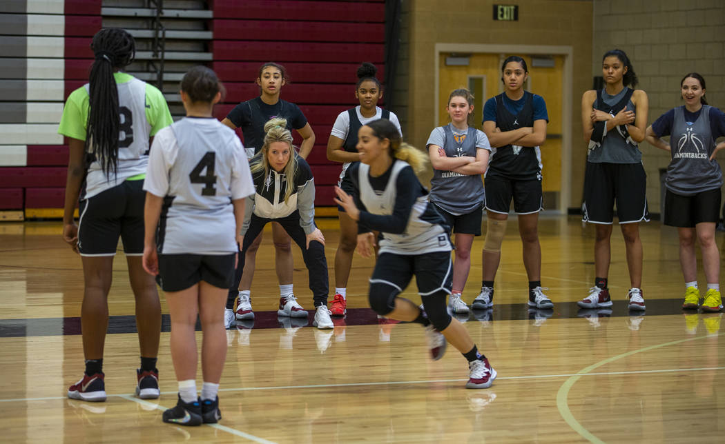 Head coach Laurie Evans, center left, looks on as her players run a play during a Desert Oasis ...