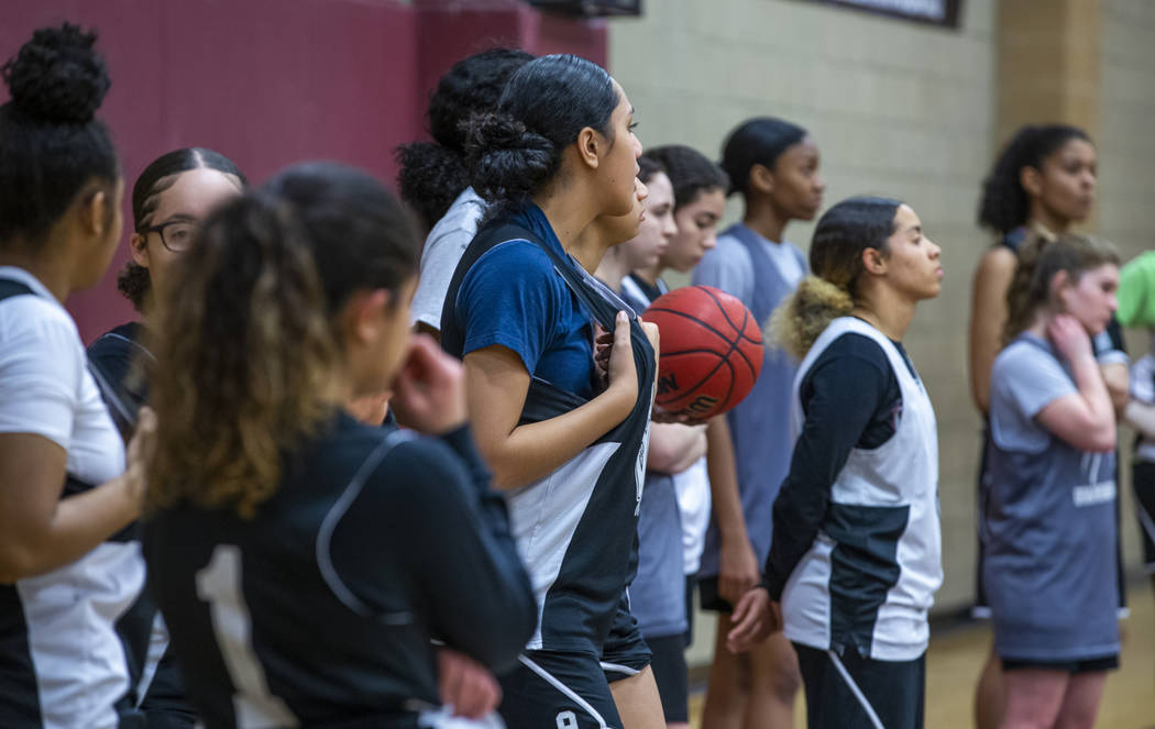 Desert Oasis girl's basketball team players stand on the base line and listen to instructions b ...