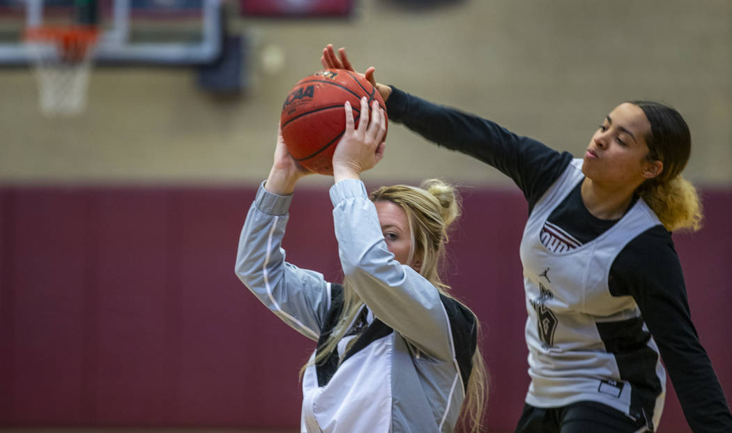 Head coach Laurie Evans, left, holds the ball tight as player Olivia Bigger attempts to swat it ...