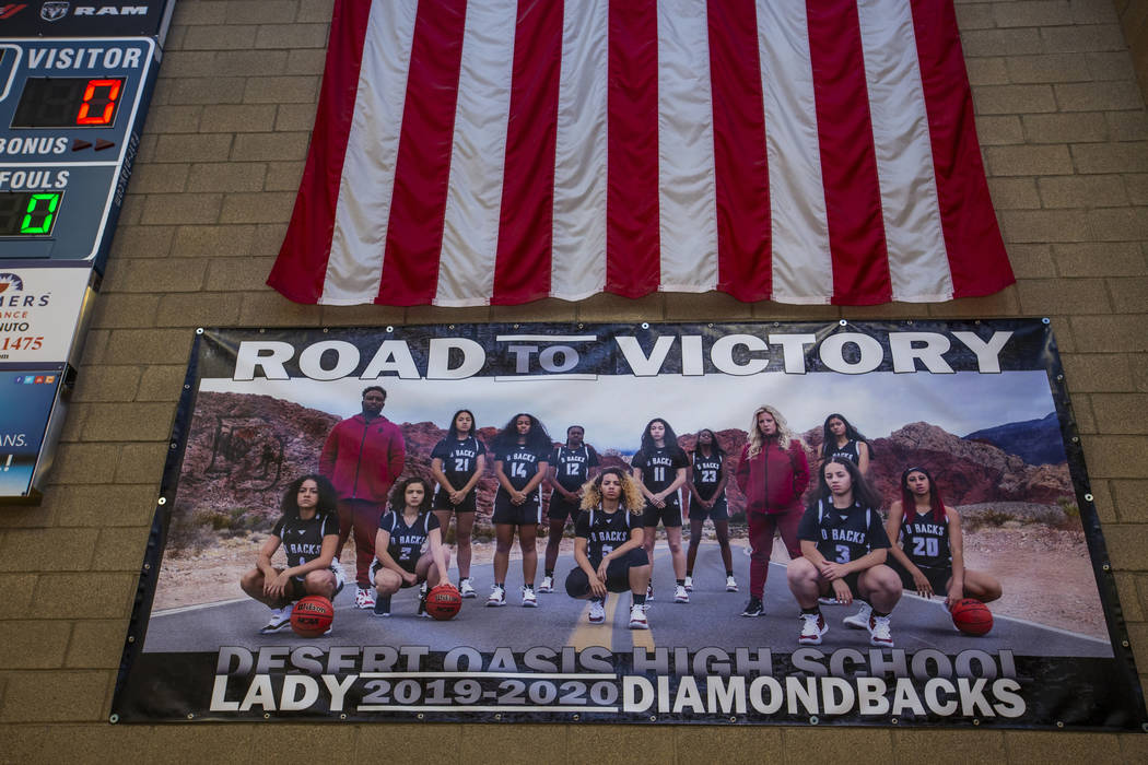 A banner hanging in the gym features the players and coaches of the Desert Oasis girl's basketb ...